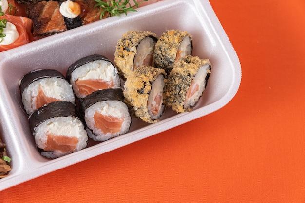 Суши в пенопластовой таре на столе
