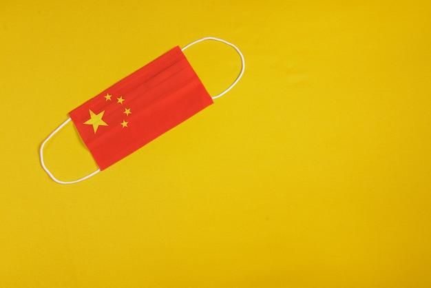中国の旗と黄色の背景にサージカルマスク