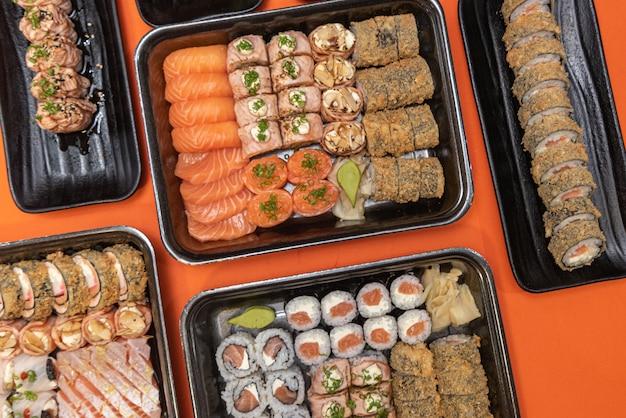 Вкусные и красивые суши на оранжевом столе