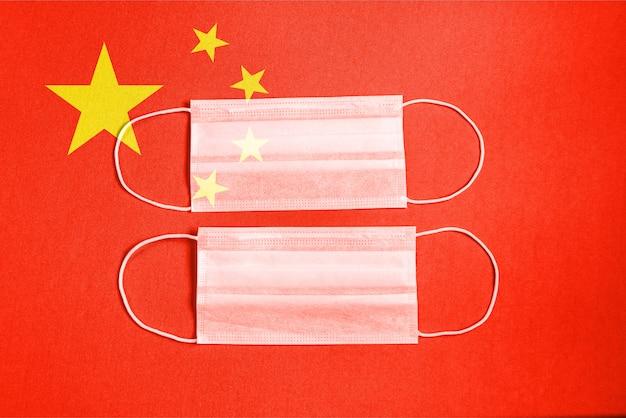 中国の旗と赤の背景にサージカルマスク
