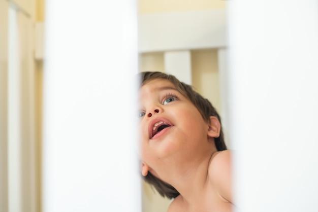 かわいい赤ちゃんの幼児 - ベビーベッドで - 観察