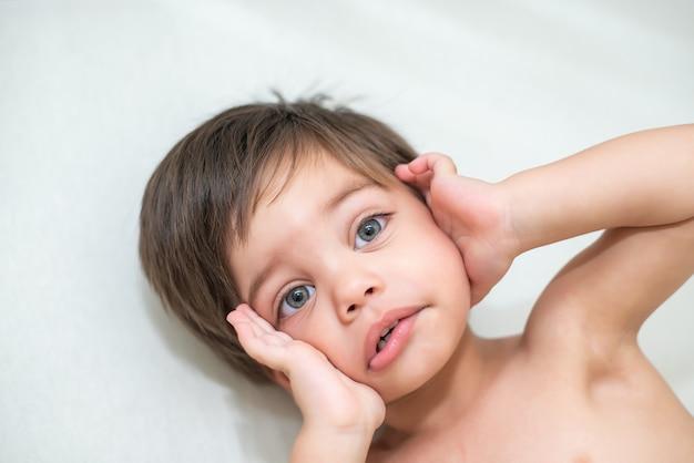 かわいい赤ちゃん男の子幼児 - ベビーベッドで - 横になっています。