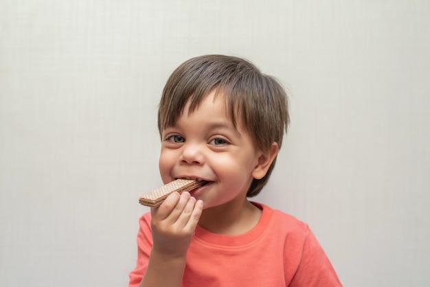 かわいい赤ちゃん男の子幼児 - ウェーハビスケットを食べる