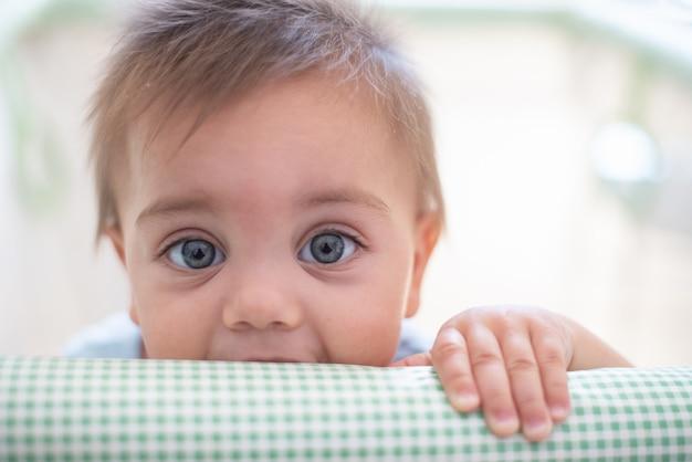ベビーサークルの中の青い目の赤ちゃん