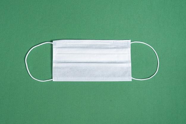 Хирургическая маска на минималистском зеленом фоне