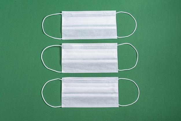 ミニマリストの緑の背景上の手術用マスク