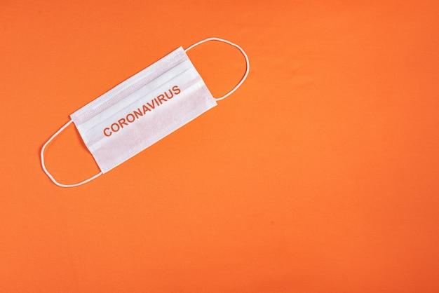 ミニマリストのオレンジ色の背景上の外科用マスク