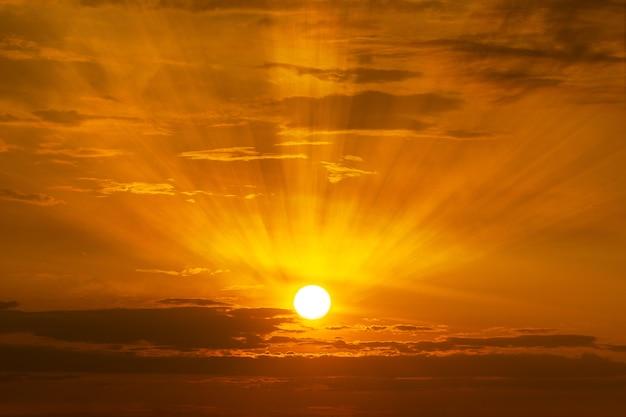 日の出や日没の時間の背景で空に輝く太陽