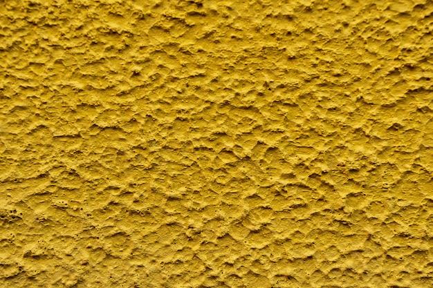 壁の黄色の色の背景の大まかなテクスチャを閉じる