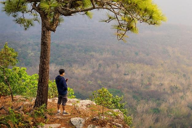 Путешественник с помощью мобильного телефона на краю утеса фоне природы