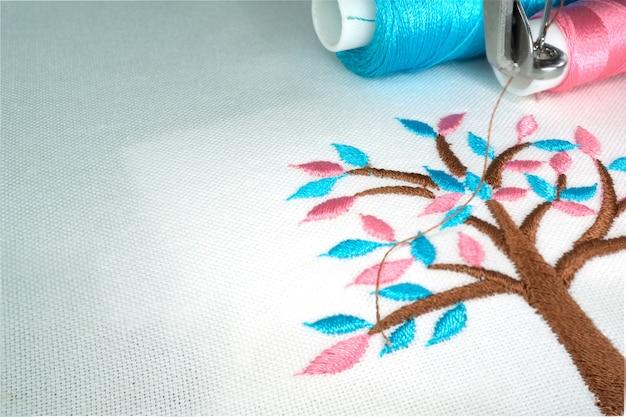 刺繍機はシアンとピンクの色の糸を持つ小さなパステルカラーの木を白い布に作る