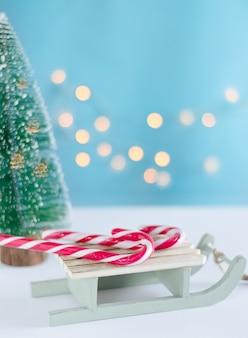 お菓子とライトと白い背景の上のクリスマスツリーの木製そり。