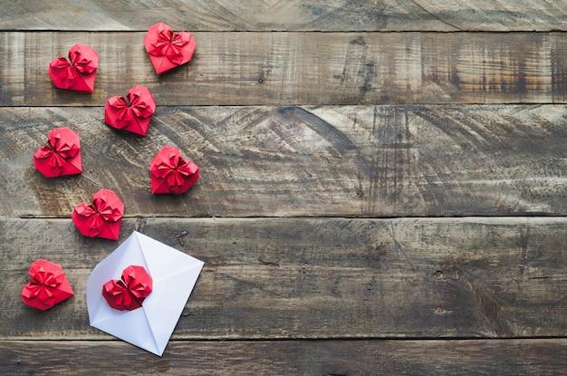 Красные бумажные сердечки с белым конвертом