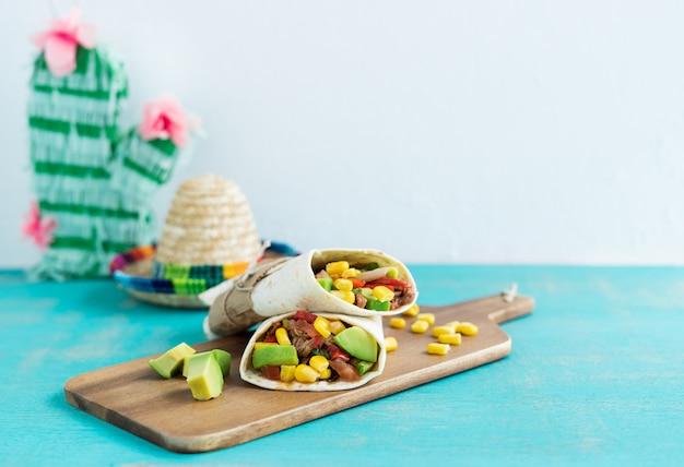 Мексиканская еда. буррито на кухонный стол на синем фоне. концепция мексиканской кухни. копировать пространство