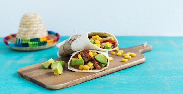 Мексиканские буррито на кухонном столе на синем фоне. концепция мексиканской кухни. копировать пространство