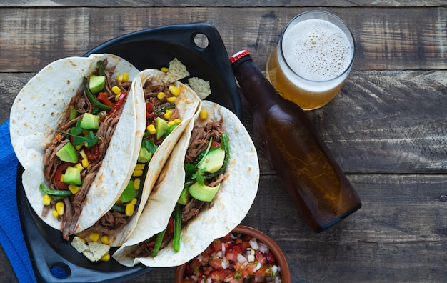 木の板に黒いトレイにビールとメキシコのファヒータ。コピースペース。メキシコ料理のコンセプトです。