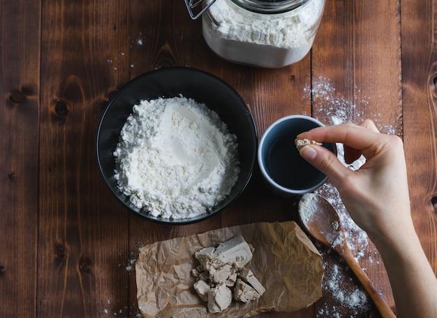Рука женщины добавляя дрожжи в воду для приготовления закваски. чаша с мукой и дрожжами на бумаге пекарня концепции. вид сверху.