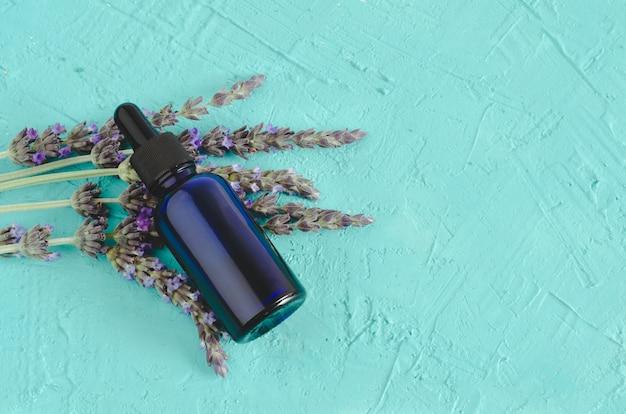 Эфирное масло лаванды. цветы и бутылка с пипеткой на синей поверхности