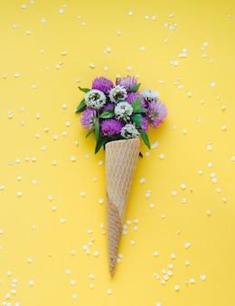 黄色の表面にアイスクリームコーンの花。フラット横たわっていた。上面図。
