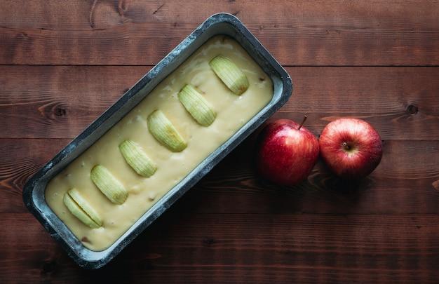 アップルデコレーションで暗い木のベースで焼く前にアップルスポンジケーキ。コピースペース。ペストリーのコンセプトです。
