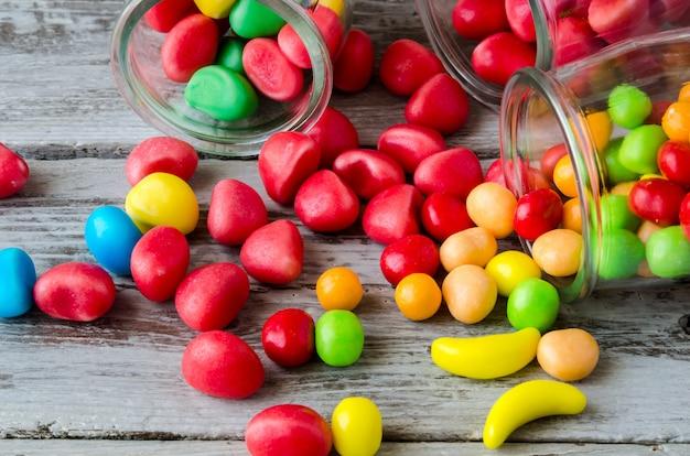Крупный план красных и желтых конфет, разбросанных по банкам