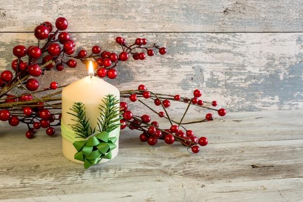 Зажженная свеча и палочка с красными ягодами