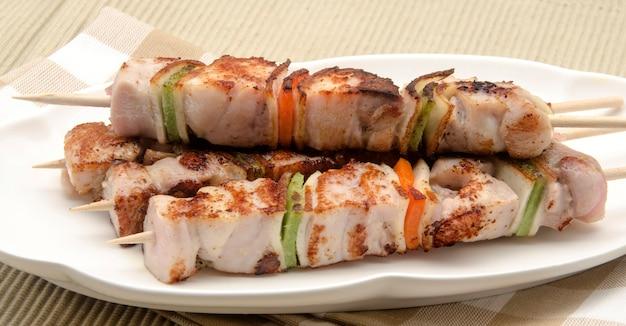 皿の上の肉の串焼き
