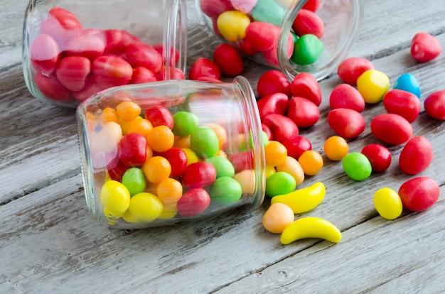 Разбросанные конфеты возле банки с разноцветными сладостями