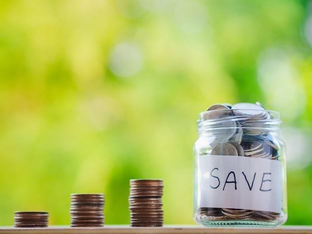 ぼかしの背景にガラスの瓶にコイン。お金を節約する金融の概念