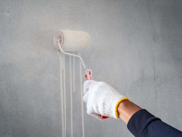 Закройте вверх руки работника используя ролик и щетку для красить стену. концепция домостроения.