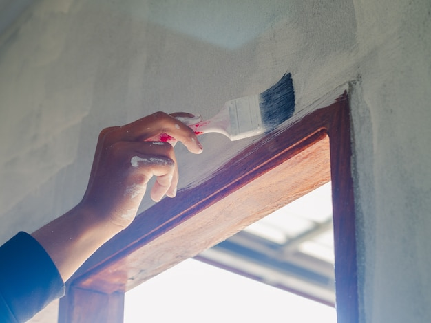 塗装壁用ローラーとブラシを使用して労働者の手のクローズアップ。家を建てるコンセプトです。