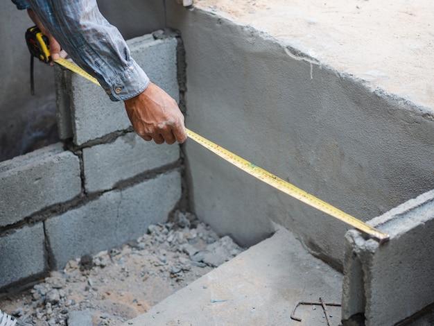 プロの建設労働者はメジャーとセメントでレンガを敷設するために測定テープを使用します。