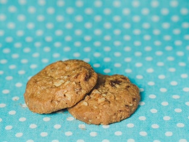 パステルブルーの水玉の背景にオートミールとレーズンのクッキー。