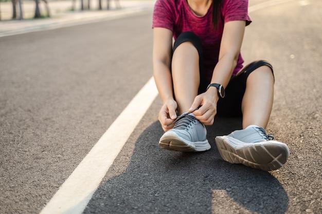 Крупный план бегуна молодой женщины связывая ее шнурки. концепция здорового и фитнеса.