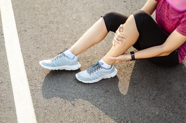 膝の怪我。ランニングトラックでのランニングトレーニングトレーニング中に筋肉の損傷を受けた後、彼女の手で膝を痛みで保持している強い運動脚を持つスポーツ女性。ヘルスケアとスポーツのコンセプトです。