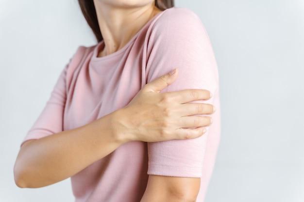 腕の痛み。腕の筋肉の痛みを伴う痛みに苦しむ美しい女性。ヘルスケアと医療の概念。