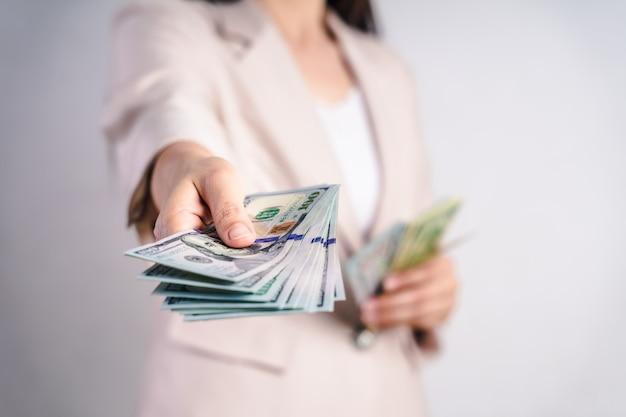 ビジネスの女性のクローズアップは私たちに白のドル札を私たちに提案します。お金の概念。
