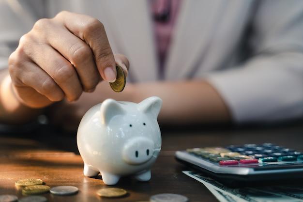Крупный план руки бизнес-леди кладя монетку денег в копилку для сохраняя денег. экономия денег и финансовая концепция