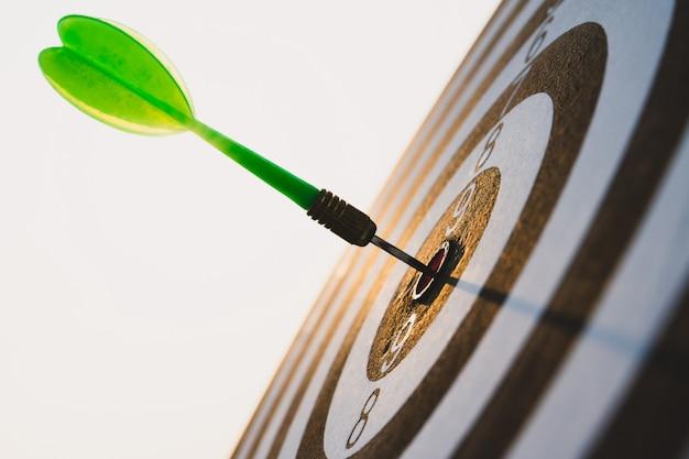 Зеленые стрелки дротиков в центре цели на небе. цель или успех цели и концепция победителя.