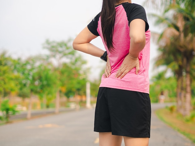 公園で背中の痛みを持つスポーツ女性