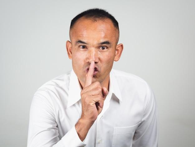 唇の沈黙ジェスチャーで指を作る男