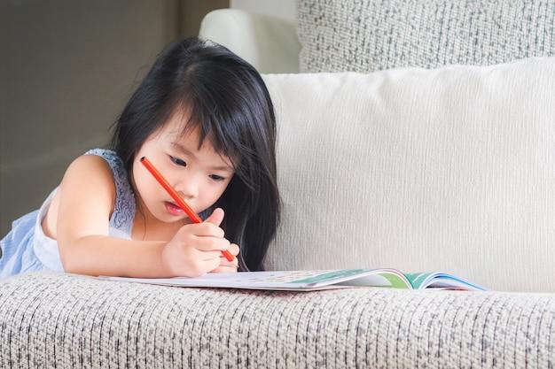 小さな女の子が赤い鉛筆で本をソファに書いています。