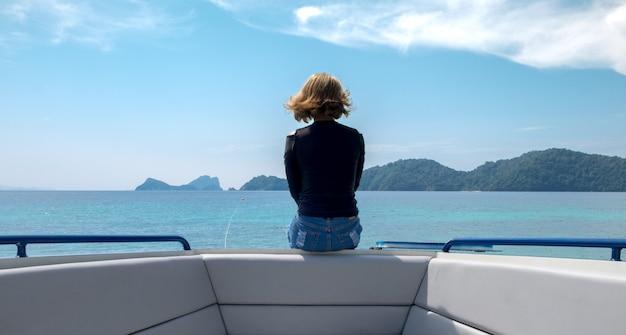 地平線を見てボートに孤独に座っている女性