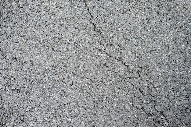 亀裂アスファルト路面のテクスチャ背景のクローズアップ