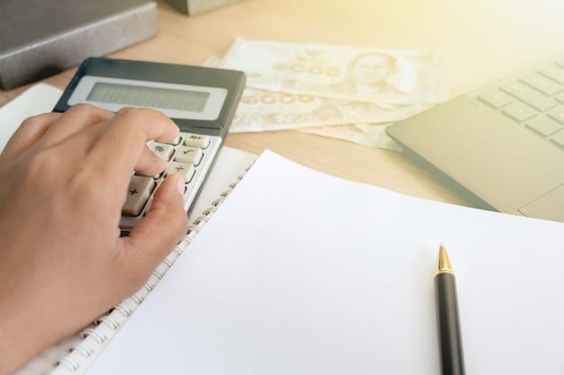 電卓とラップトップを使用して金融税を計算するための女性