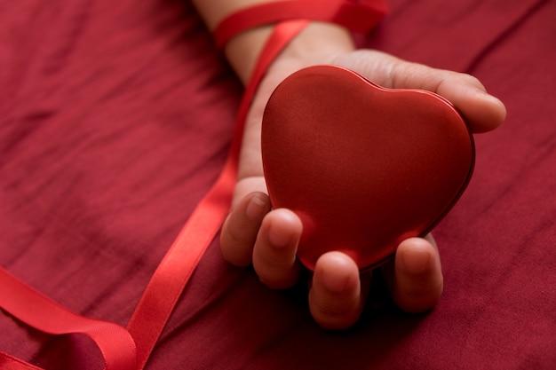 赤い背景に手の中の心。心を保持する、セクシーなバレンタインのコンセプト。