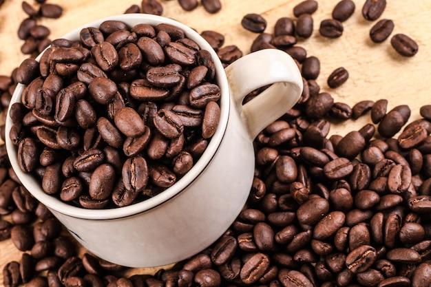 コーヒーカップと木製の背景のコーヒー豆。上面図。