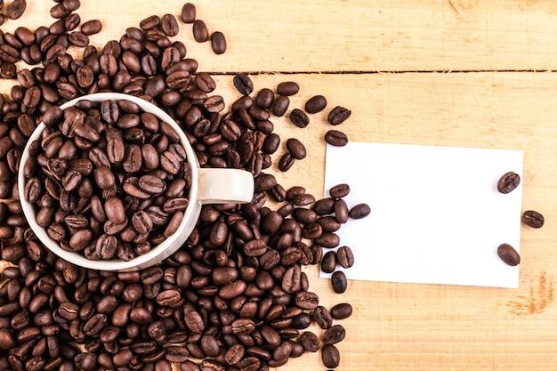 コーヒーカップと木製の背景のコーヒー豆。コピースペースのための空の紙で平面図