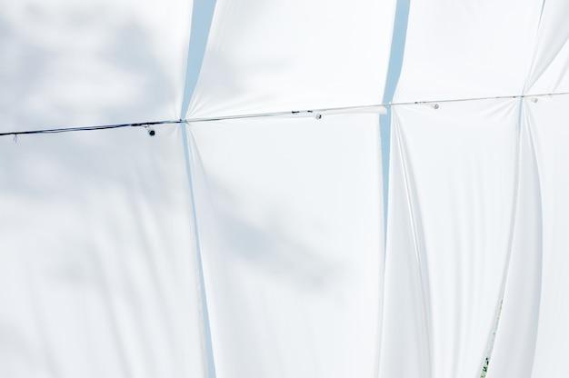 青い空の上に日よけ。白いキャンバス屋根の間から下から空と雲の眺め