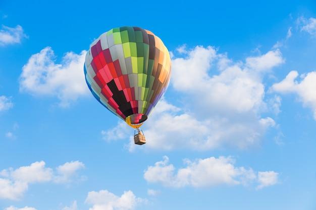 青い空を背景にカラフルな熱気球